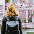 Girl standing with a backpack in front of an apartment.