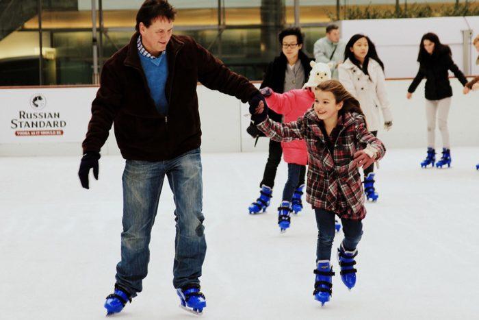 A man and his daughter ice-skating.