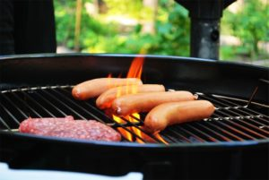 hot dogs and hamburger patty on a grill