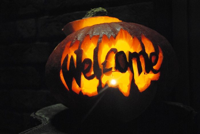 A pumpkin carved into the word welcome.