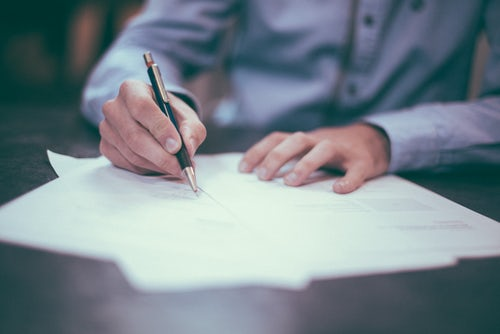image of a person signing paperwork to represent lease signing.