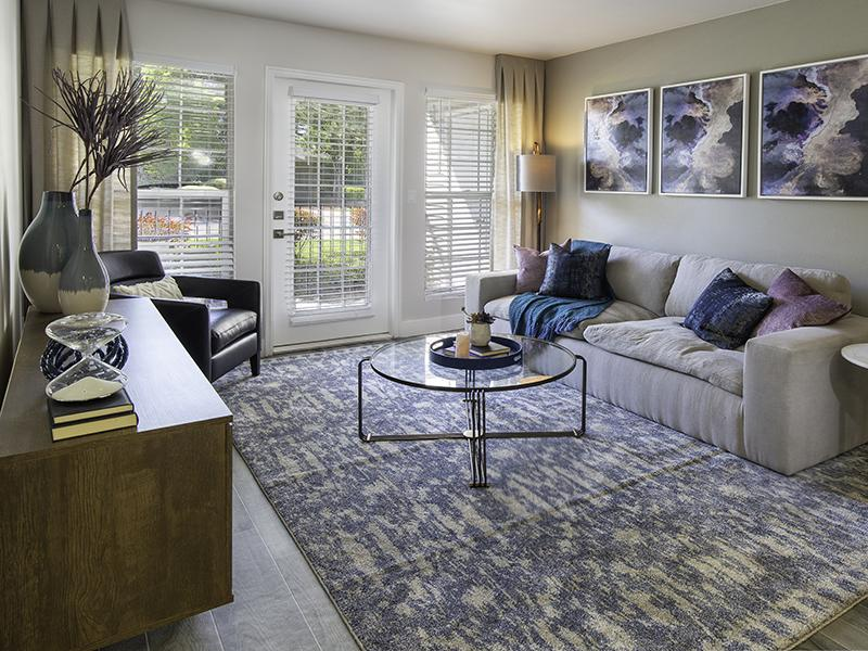 Taylorsville, UT Apartments - Maison's Landing Living Room with Wood-Style Flooring and Access to Patio or Balcony