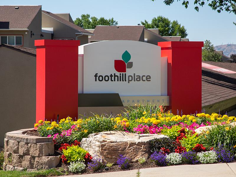 Pet-Friendly Apartments in Salt Lake City, UT - Foothill Place Apartments Front Sign with Lush Landscaping and Clubhouse