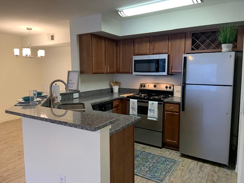 Stainless Steel appliances and wood style flooring in the kitchens at Providence Lakes Apartments.